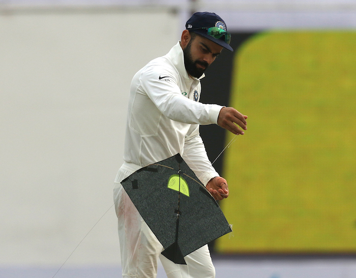 Virat Kohli deals with a stray kite on the field
